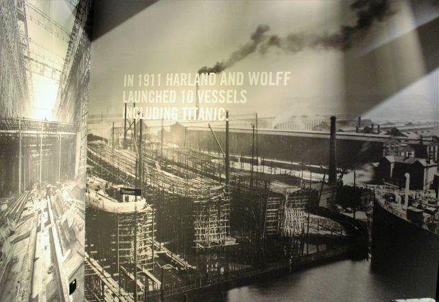 """Foto aus der Ausstellung der Titanic Experience mit einer Werftanlage, auf der mehrere Scgiffe parallel entstehen. Text: """"In 1911 Harland and Wolff launches 10 vessels including Titanic."""