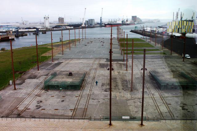 Blick auf die ehemalige Werft der Titanic. Dieses wird durch Metallstangen symbolisiert. Dahinter ein Hafenbecken.