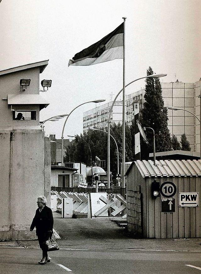 Eine ältere Frau passiert einen Kontrollposten der DDR-Grenztruppen. Sie wird aus einem Turm beobachtet, dahinter die Flagge der DDR.
