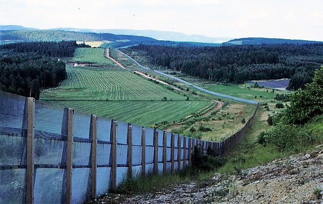 Ein langer Grenzzaun aus Metall durchschneidet eine Landschaft mit Wiesen und Wald. Eine breite Schneise wurde angelegt, damit die DDR-Grenzer freies Schussfeld hatten.