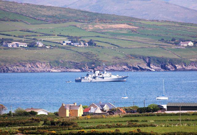 Das Marineschiff Orla liegt im Ventry Harbour - einer Meeresbucht. Das Schiff ist grau, das Meer blau. Im Vorder- und Hintergrund einige Häuser am Ufer.