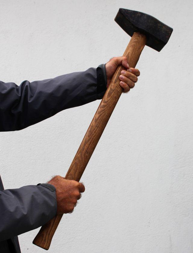 Vorschlaghammer, sieben Kilogramm Gewicht, wird am hözernen Stiel von zwei Händen gehalten.