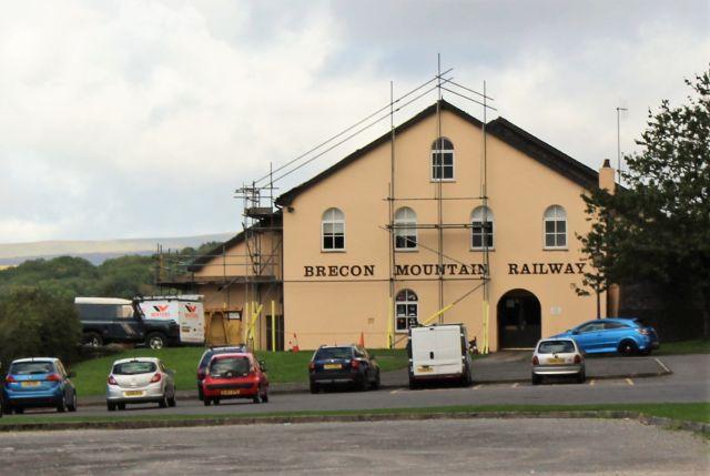 Hellbraunes Gebäude mit der Aufschrift Brecon Mountain Railway. Davor Pkw in rot, schwarz, weiß und silber.