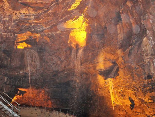 Wasser fließt über die Wände einer rötlich-braun leuchtenden Höhle.