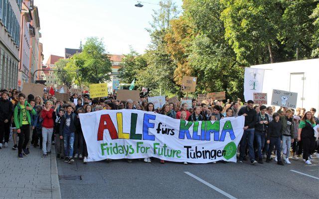 """Demonstranten von Fridays for Future auf der Wilhelmstraße in Tübingen. Die Teilnehmer in der ersten Reihe tragen ein großes weißes Transparent mit dem Text """"Alle fürs Klima. Fridays for Future Tübingen""""."""