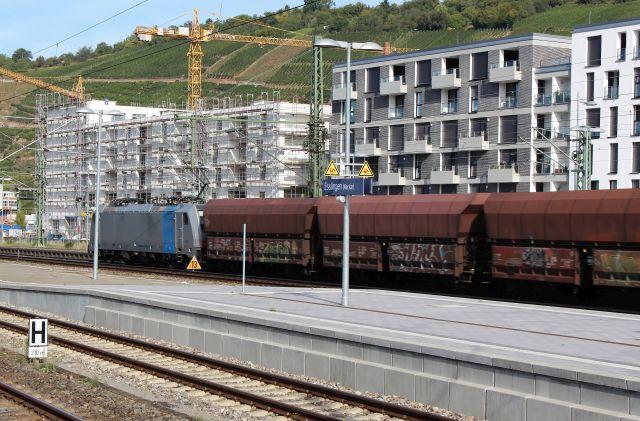 Ein Güterzug mit braunen Waggons fährt an Neubauten in Esslingen am Neckar vorbei.