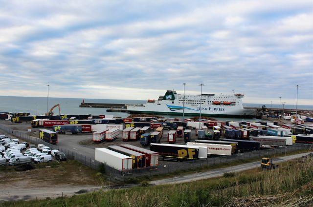 Blick auf den Hafen im irischen Rosslare am hereinbrechenden Abend. Blauer Himmel mit weißen Wolken. Eine Fähre von Irish Ferries hat angelegt. Im Vordergrud wartende Lkw.