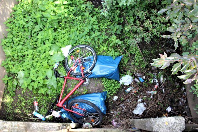 Ein Fahrrad und Müllsäcke in einem kleinen Regenrückhaltebecken.