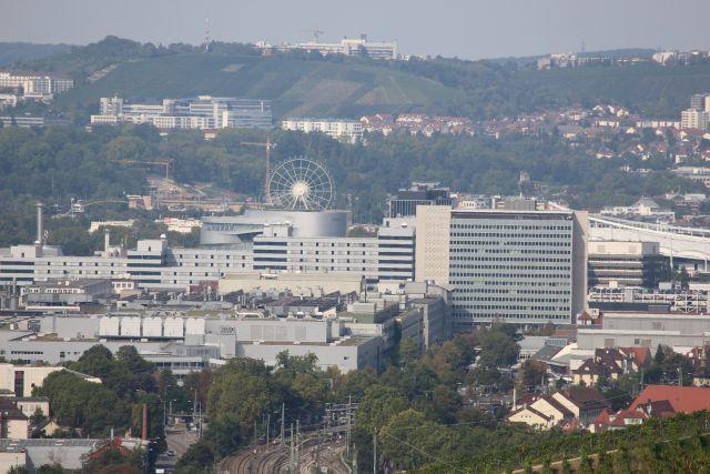 Das Riesenrad erhebt sich hinter Industrieanlagen.