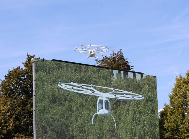 Ein elekrisch betriebener Volocopter - einer Drohne ähnelnd - über einer Leinwand, auf der er eingespielt wird.