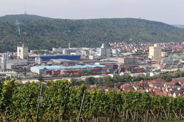 Im Vordergrund grüne Blätter eines Weinbergs, dahinter Industriaanlagen am Neckar mit Schottbergen und Containern.