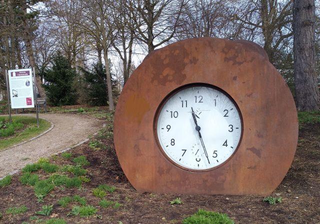 Große weiße Uhr mit schwarzen Zeigern und einem dunkelbraunen Metallrand.