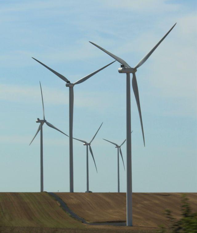 Mehrere Windenergieanlagen vor blauem Himmel.