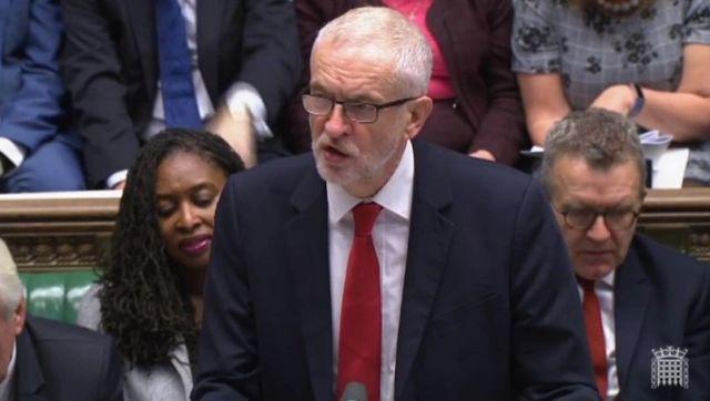 Jeremy Corbyn im dunklen Anzug, weißem Hemd und roter Krawatte. Er trägt eine Brille und hat graue Haare.