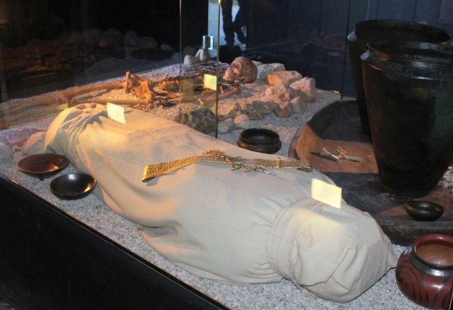 Ausstellung zu den aufgefundenen Bestattungsarten: In eine Stoffhülle eingelegte Leiche bzw. ein Skelett.