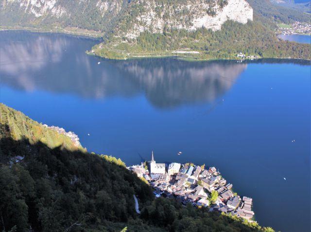 Blick auf Hallstatt am gleichnamigen blauen See, in dem sich die Berge spiegeln.