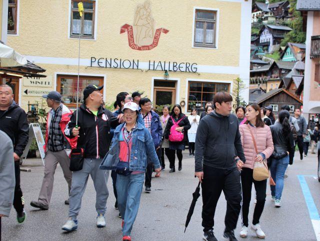 Besuchergruppe aus Asien in einer engen Gasse in Hallstatt.