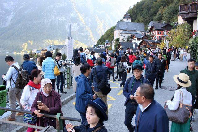 Chinesische Besucher über dem Hallstätter See. Sie Fotografieren mit Smartphones und Kameras.