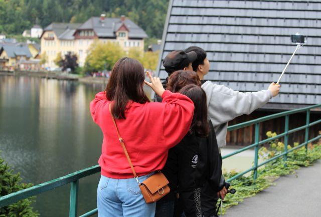 Eine Familie nimmt sich mit dem Smartphone am Stick selbst auf.