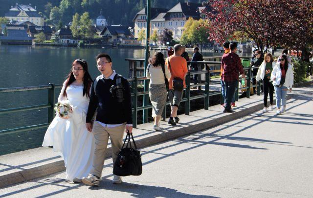 Braut im weißen bodenlangen Hochzeitskleid, der Bräutigam trägt den nentsprechen Anzug noch in der Tasche.den