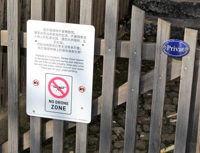 Ein kleines Schild 'Privat' an einem Gartentor und ein Hinweisschild der Gemeinde, Besucher sollten die Privatsphäre der Einwohner achten.