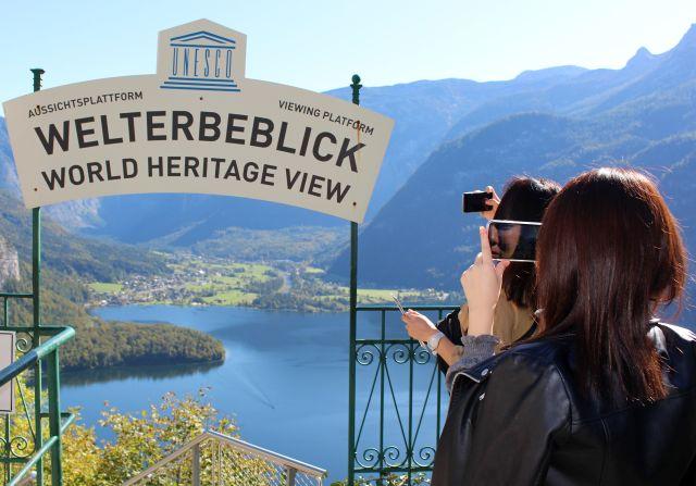 Ein Schild UNESCO-Welterbeblick. Daneben zwei Frauen von hintebn, die mit dem Smartphone sich selbst bzw. die Landschaft aufnehmen.