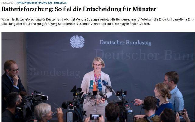 """Bundesministerin Karliczek in heller Kleidung umringt von Journalisten mit Mikrofonen. Überschrift """"Batterieforschung: So fiel die Entscheidung für Münster""""."""