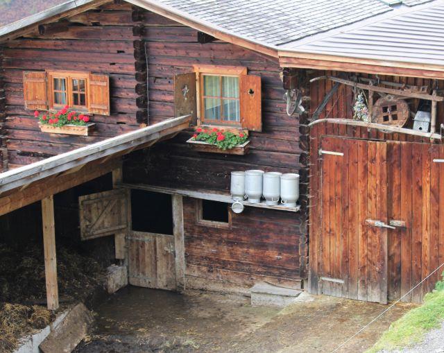 Bauernhaus aus Holz mit rot blühenden Blumen vor dem Fenster. Darunter ist eine Miste zu sehen.vier Milchkannen. Das Ge