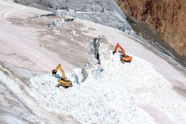 Zwei Bagger mit oangener Farbe wühlen in einem weißen Gletscher.