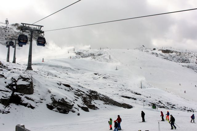 Seilbahn und darunter Skifahrer und Beschneiung.