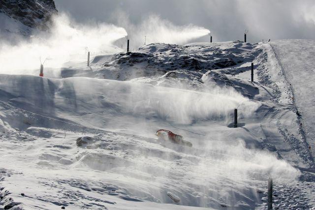 Schneelanzen blasen Kunstschnee auf die Piste. im fliegenden Schnee eine Pistenraupe und schemenhaft Skifahrer.