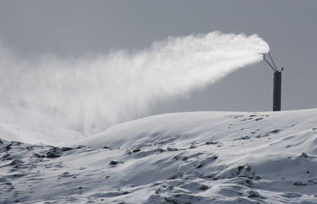 Kunstschnee aus einer Schneelanze am Hintertuxer Gletscher. Der Schnee weht wie eine große Fahne nach links weg.