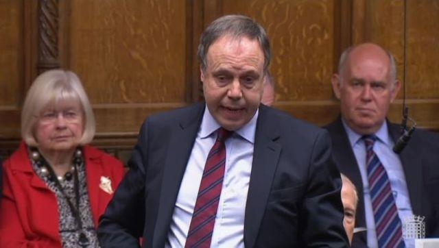 Nigel Dodds im dunkelblauen Anzug mit weißem Hemd und roter Krwatte.