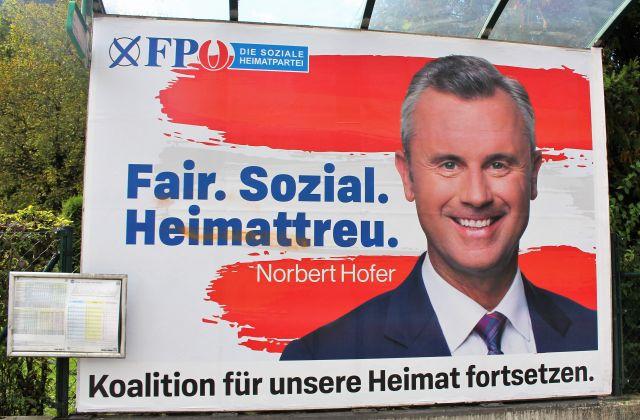 """Norbert Hofer auf einem Plakat der FPÖ, das in weißen und roten Farbtönen gehalten ist. Text """"Fair. Sozial. Heimattreu""""."""