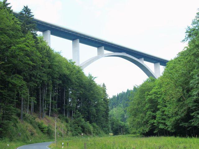 Hohe Betonbrücke mit bogenförmiger Struktur über einem grünen Tal.