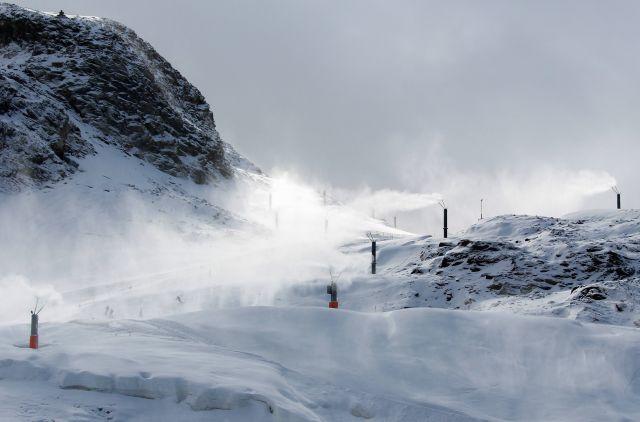 Skifahrer auf einer Piste, die mit Schneelanzen (dünnen, hohen Rohren) beschneit wird. Die Aufnahme entstand auf dem Hintertuxer Gletscher Anfang Oktober.