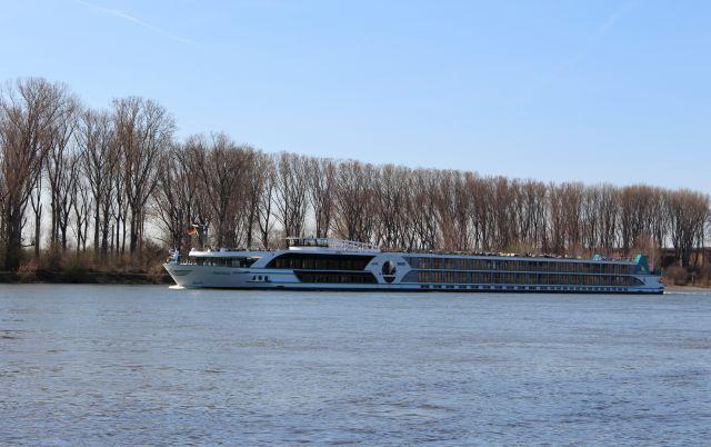 Flusskreuzfahrtschiff auf dem Rhein. Im Hintergrund Bäume am Ufer, im Vordergrund die Wasserfläche des Rheins. Ds Schiff ist langgestreckt, auf dem Oberdeck sitzen Passagiere.