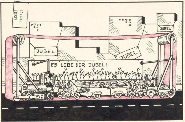 Ein Fahrzeug mit Jubel-Aufschriften wird parallel zu DDR-Führungspersonal gefahren.