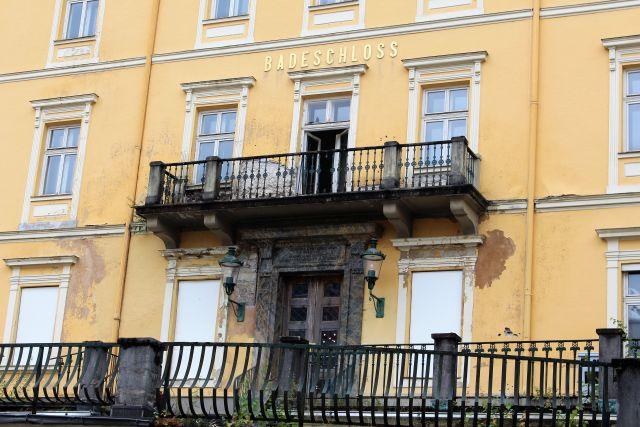 Maroder Verputz am Hotel Badeschloss. Gelbliche Fassade. Balkongitter schwarz.