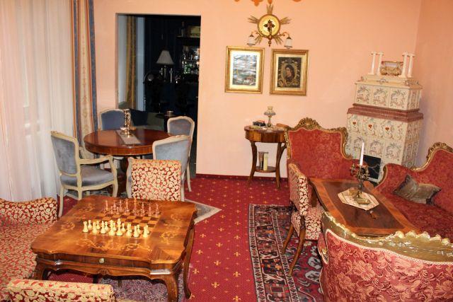Einrichtung im Stil des 19. Jahrhunderts. Schachspiel auf einem feinen Holztisch. Die Sitzgelegenheiten und der Teppich in rötlichen Tönen gehalten-