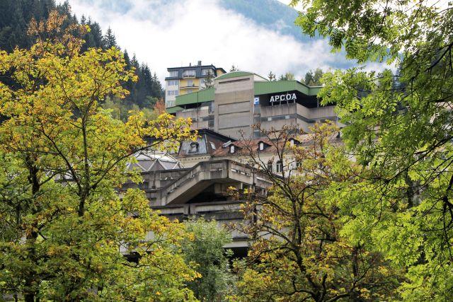 Das Kongresszentrum und das Parkhaus aus Beton stören das malerische Bild von Bad Gastein. Ringsum grüne Blätter von Bäumen.