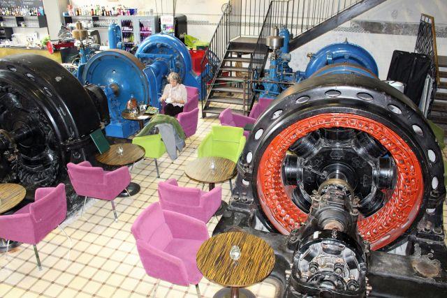 Eine Frau sitzt beim Mittagessen. Bunte Sitzgelegenheiten zwischen den Maschinen des ehemaligen Kraftwerks.