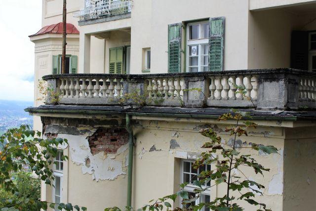 Teile des hellen Verputzes sind abgefallen. Der Balkon hat stark gelitten.
