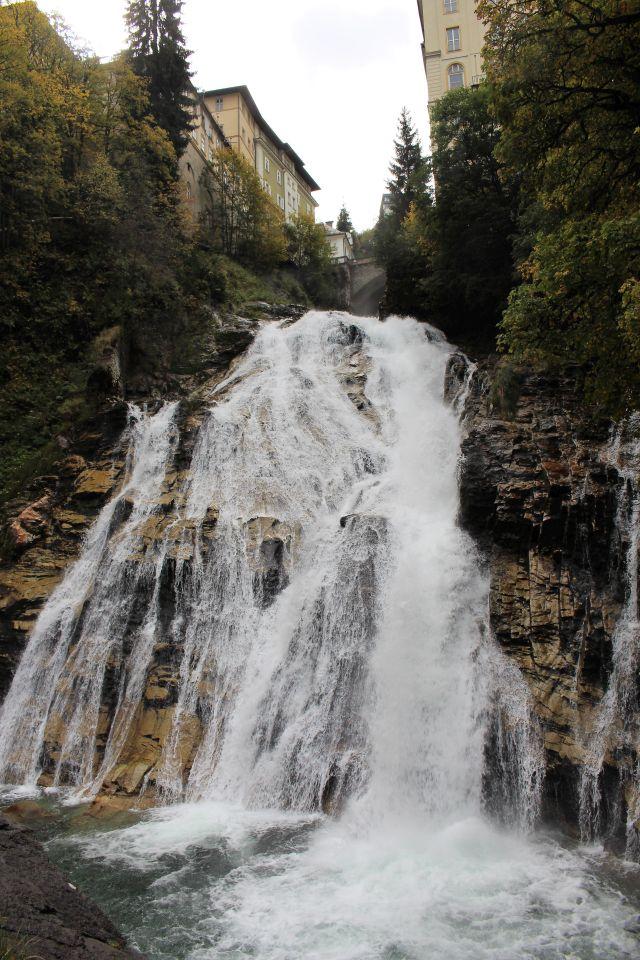 Ein Wasserfall stürzt sich zwischen hochen Gebäuden in die Tiefe.