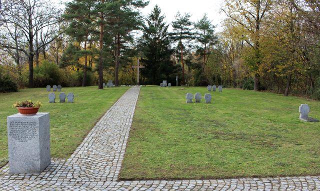 Grüner Rasen mit steinernen Kreuzen und einem Holzkreuz.
