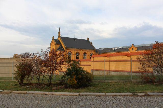 Das 'Gelbe Elend'. Die Haftanstalt wurde aus gelblichen Backsteinen errichtet. Links eine moderne Betonmauer, rechts aus Backsteinen.