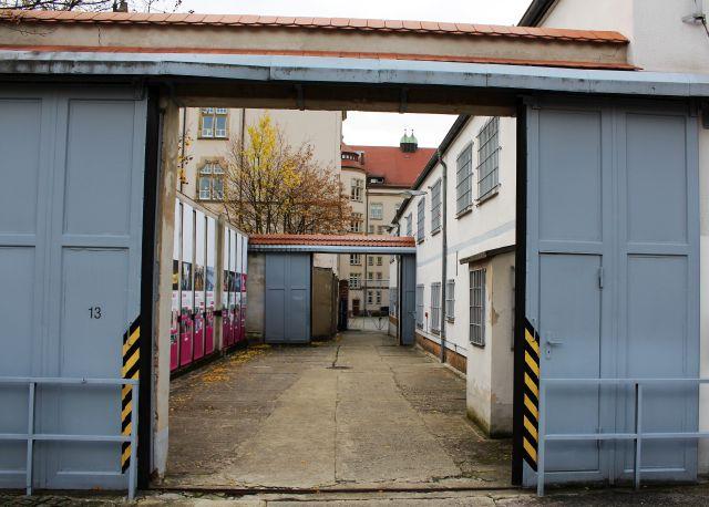 Ein graues Tor, gefolgt von einem weitern Tor. Rechts ein helles Gebäude.