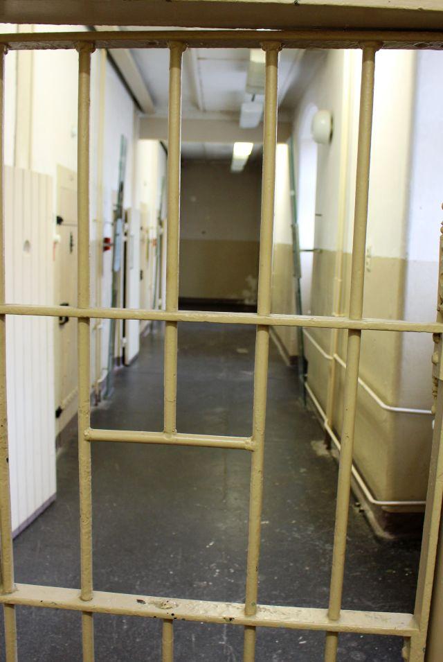 Starkes Gitter versperrt einen Gang. Dahinter Zellentüren.