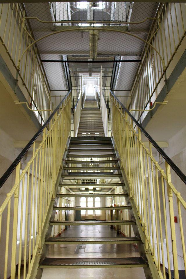 Eine Treppe führt nach oben in die nächste Etage mit Zellen.