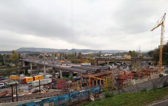 I Vordergrund die neue Bahnbrücvke über den Neckar, rechts die alte Brücke in bräunlichen Farben.